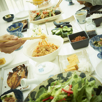 食卓に並んだ料理と食事をする男性の手