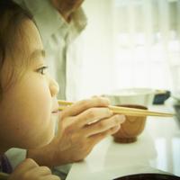 女の子の横顔と箸を持つ父親の手
