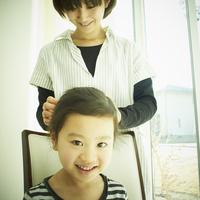 女の子の髪を結う母親
