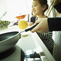 キッチンに立つ女の子と料理をする母親の手元