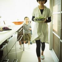 キッチンに立つ女の子と料理を運ぶ母親