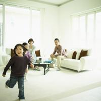 リビングルームを走る男の子とソファに座るファミリー