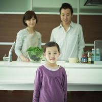 笑顔の女の子とキッチンから見守る両親