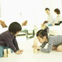 積み木で遊ぶ2人の子供とソファに座る両親
