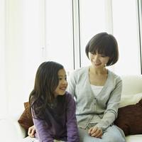 ソファに座る女の子と母親