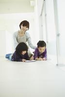 お絵かきをする男の子と女の子と見守る母親