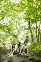 森林の岩の上に座る4人の子供達