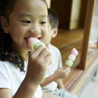 串団子を食べる女の子と男の子 11070010836| 写真素材・ストックフォト・画像・イラスト素材|アマナイメージズ