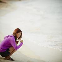砂浜で拾ったサンゴの欠片を見つめる女性