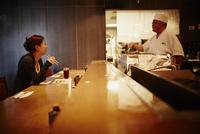カウンターで向い合う料理人と女性客