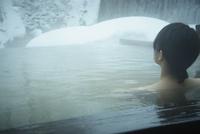 冬の露天風呂に入浴する女性の後姿