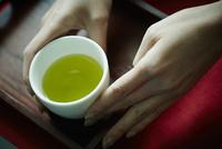 緑茶が入った湯のみに添えた女性の手