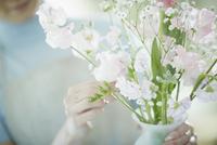 花瓶に花を活ける女性