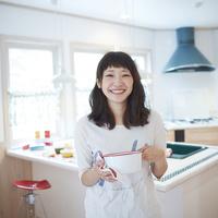 鍋を持つ笑顔の若い女性