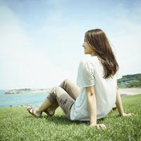 芝生の上に座り海を眺める女性