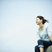 防波堤に座る女性と青空