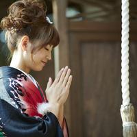 神社で手を合わせる振袖姿の女性