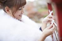 おみくじを結ぶ振袖姿の女性 11070016016| 写真素材・ストックフォト・画像・イラスト素材|アマナイメージズ