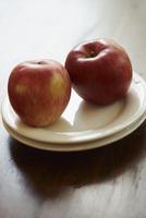 重ねた皿の上の2個のリンゴ