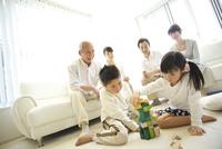 積木で遊ぶ子供達とソファに座る両親と祖父母