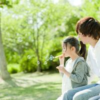シャボン玉で遊ぶ女の子と父親