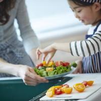 サラダを作る女の子と母親