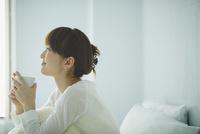 ベッドでコーヒーを飲む女性
