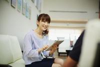 タブレットPCを持ち商談をする女性