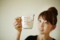 計量カップで牛乳を量る女性