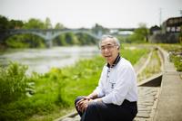 川辺に座る笑顔のシニア男性