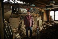 作業着姿の炭焼き小屋の笑顔のシニア男性