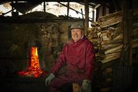 炭焼き窯の前に座る笑顔のシニア男性