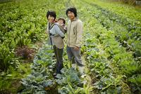畑に立つ農家ファミリー