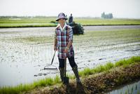 水田に立つ笑顔の農夫
