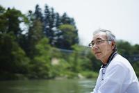 川を眺めるシニア男性