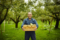 ラフランスが入った箱を持つ笑顔の農夫