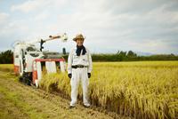 稲田のコンバインと笑顔の農夫