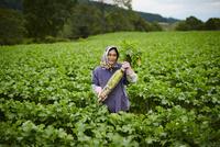 ダイコンを持つ笑顔の農婦
