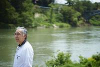 川を眺める笑顔のシニア男性