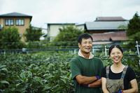 ナス畑の前に立つ笑顔の農家夫婦