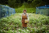 畑に立つ笑顔の農婦 11070018586| 写真素材・ストックフォト・画像・イラスト素材|アマナイメージズ