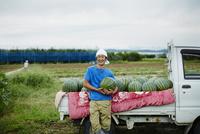 スイカを積んだトラックとスイカを抱える笑顔の農夫