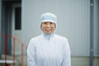 食品衛生服を着た笑顔のシニア女性