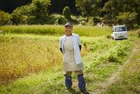 畑の前に立つ笑顔の農夫
