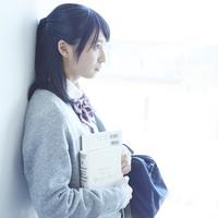 壁に寄りかかる女子学生の横顔