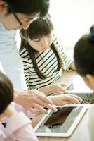 教室で先生と一緒にタブレットPCを操作する小学生