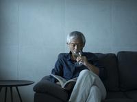 ワインを飲みながら本を読むシニア男性