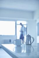 テーブルの上のコーヒーポットとカップと男性