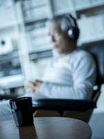 テーブルの上のコーヒーとヘッドフォンで音楽を聴くシニア男性