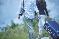 スーツケースをひいて歩くミドル夫婦